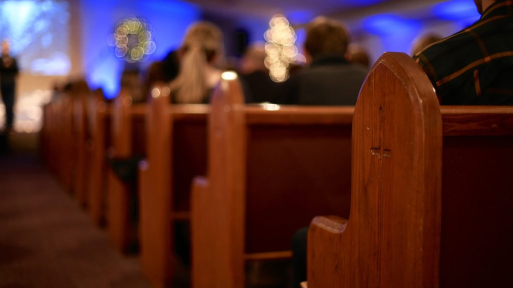 Congregation members sitting in church pews