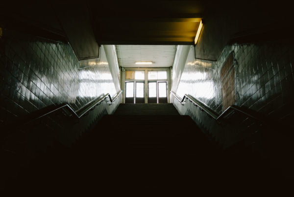 Dark staircase leading up to sunlit doors to outside