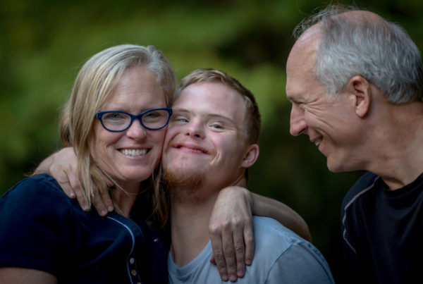 Young man with Down syndrome and woman hug each other while an older man looks on joyfully