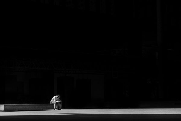 A lone man sits on a bench, a single beam of light across the floor