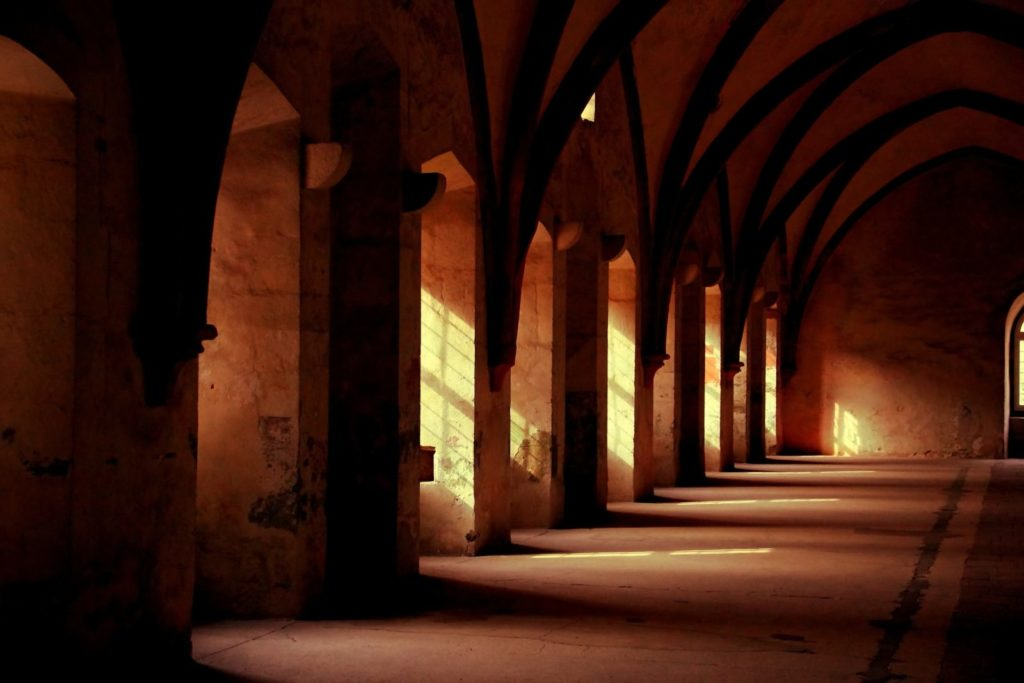 Light streams through the windows in a monastery corridor
