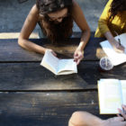 Young people sit together at a picnic table, studying a book and writing in their journals as discipleship.
