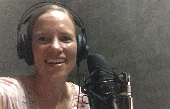 Nancy Smith-Mather speaks into mic at radio station