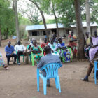 South Sudanese Christians sit in blue plastic chairs outdoors