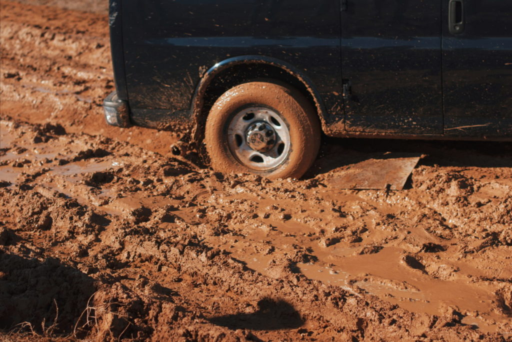 The wheel of a van is stuck in the mud.