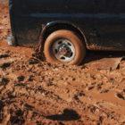 The wheel of a van is stuck in the mud.