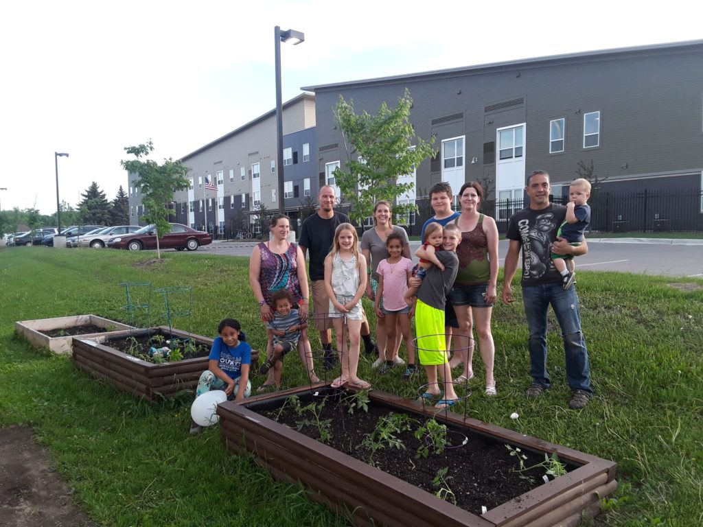 A dozen people stand behind raised garden beds sprouting small crops