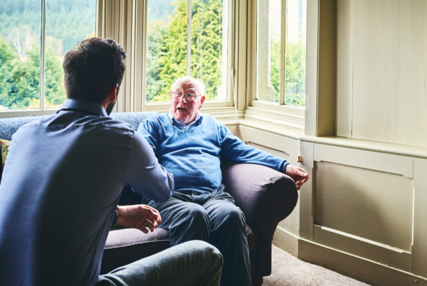 Older man talking with younger man in brightly lit nursing home to represent a pastoral visit