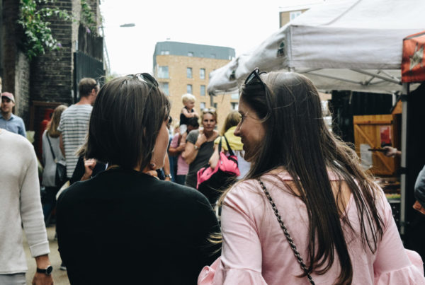 Two women talk while walking down a busy London street