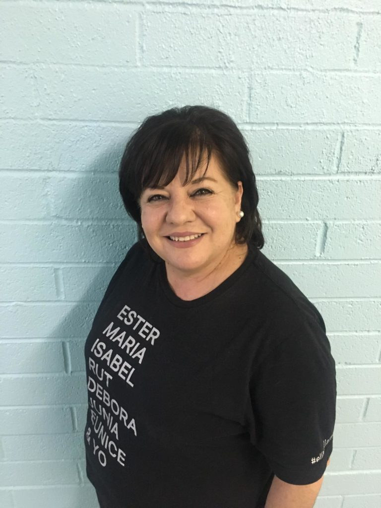 A Hispanic woman smiles broadly, wearing a black shirt with the names of biblical women on it