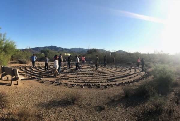 Women walk a prayer labyrinth in the hot Arizona sun