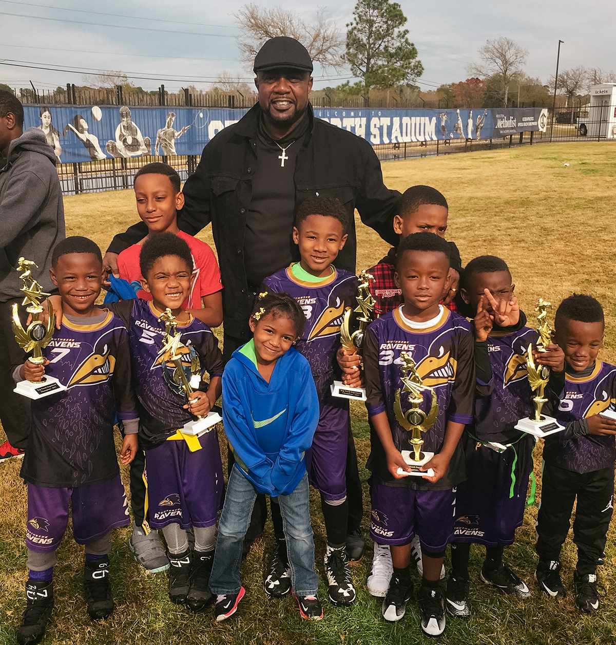 Nine boys in football jerseys hold trophies, while their coach stands behind.
