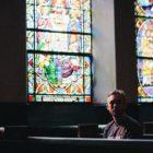 Man sitting alone in empty, dying church