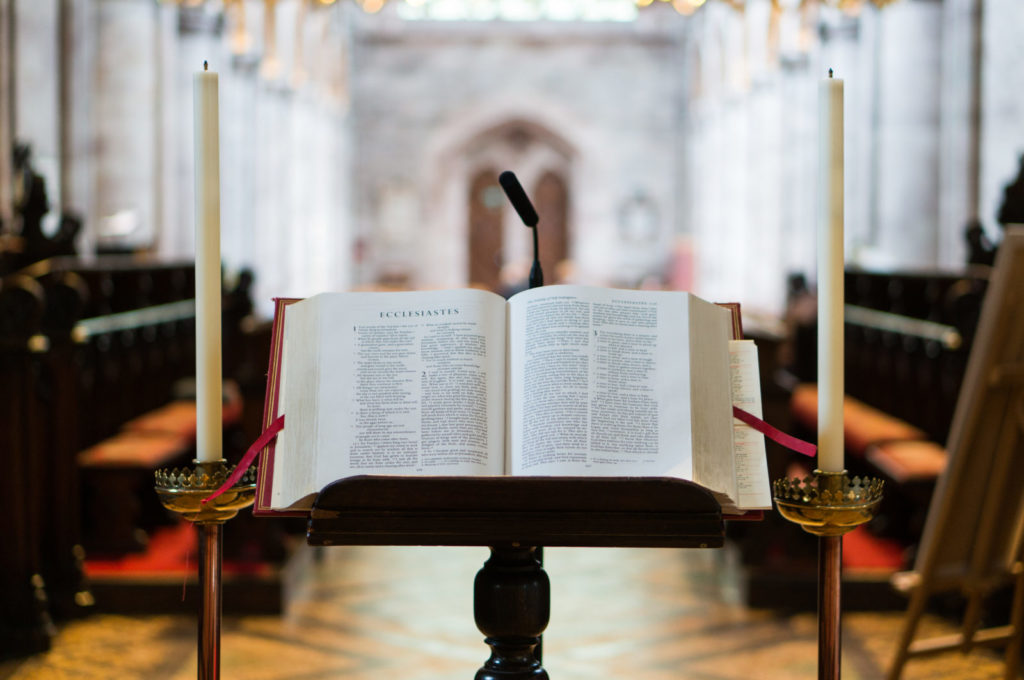 An ornate Bible sits open on a stand between two candlesticks in Hereford Cathedral