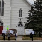 A small crowd of people stand on the sidewalk outside of a historic-looking church building, holding signs that express support of immigrants