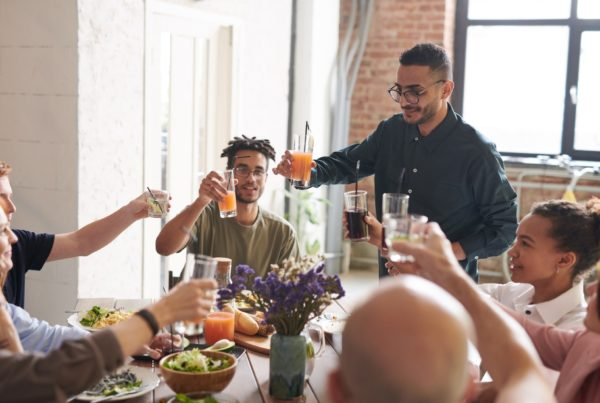 A group of people around a table raise half-full glasses for a toast
