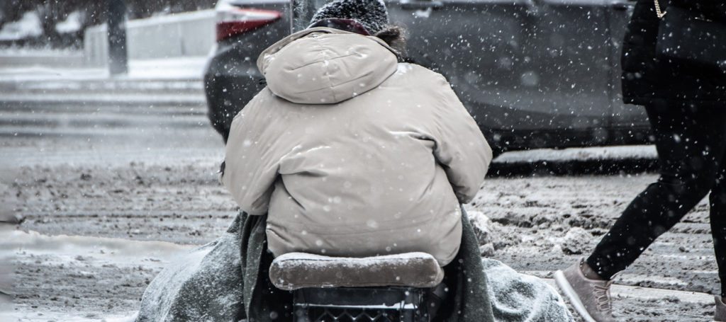homeless person sitting in on milk carton in snow