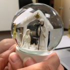 Two hands hold a snow globe with Mary, Joseph, and Jesus inside