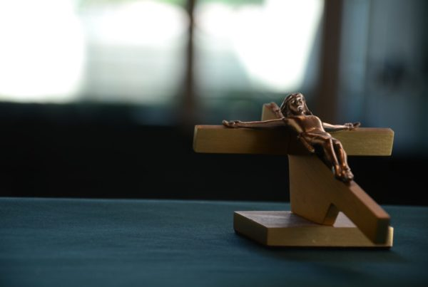 Small wooded figure of Jesus nailed to a cross sits on a table