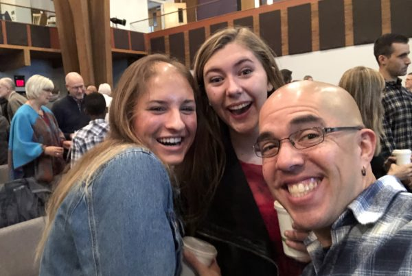 Two college women and a 40-something man with glasses and a shaved head pose for a selfie in a church sanctuary