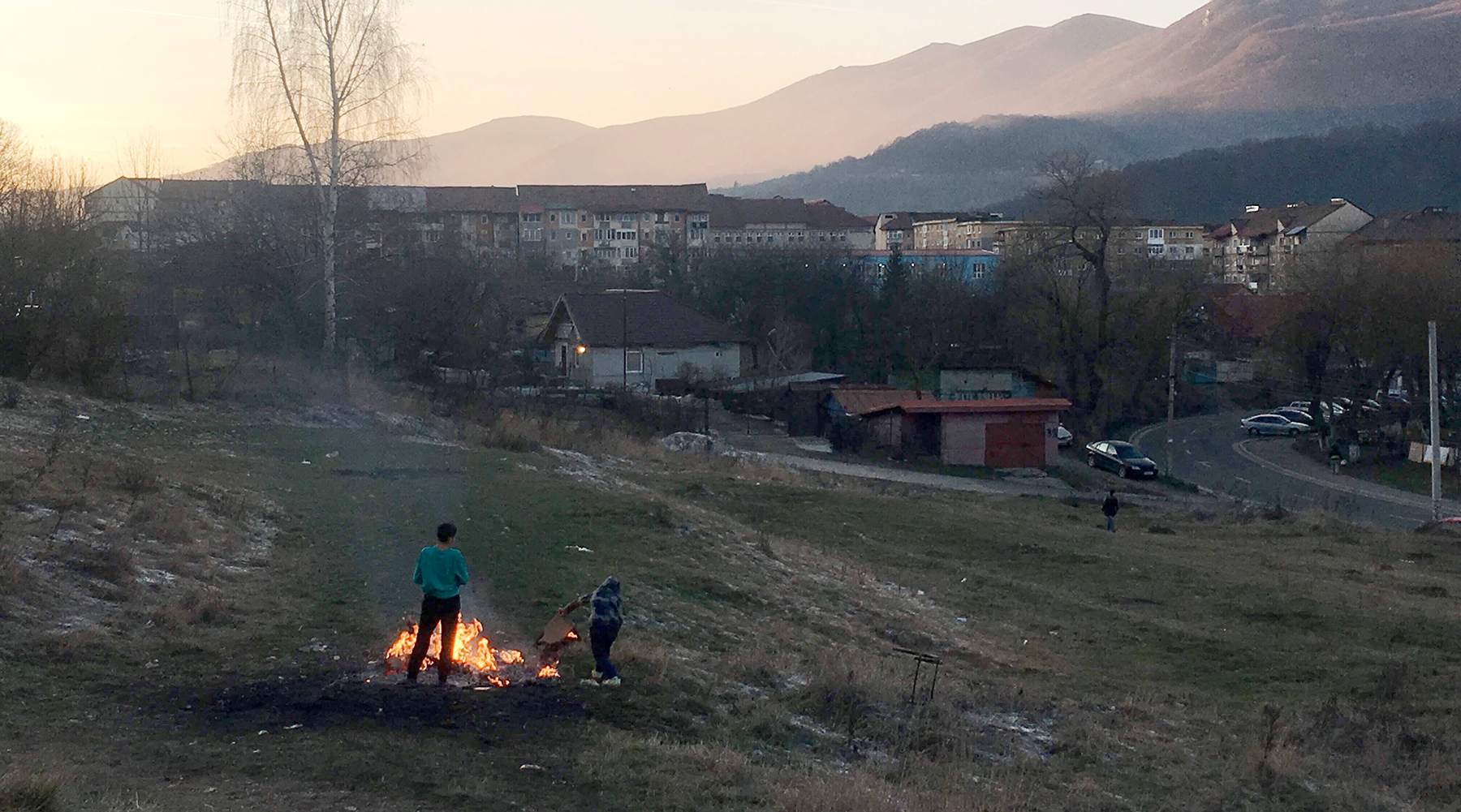 Two boys stand near a bonfire on a grassy hillside. Apartment buildings and mountains tower in the background.
