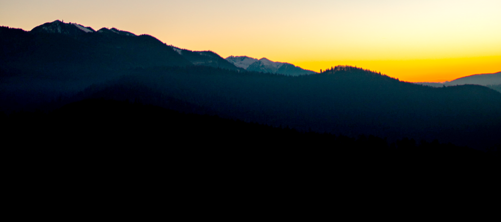 Orange sunlight hovers over the peaks of a backlit mountain range.