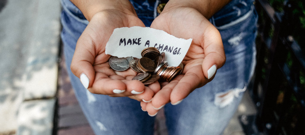 "Open hands holding coins and a note that says ""Make a change"""