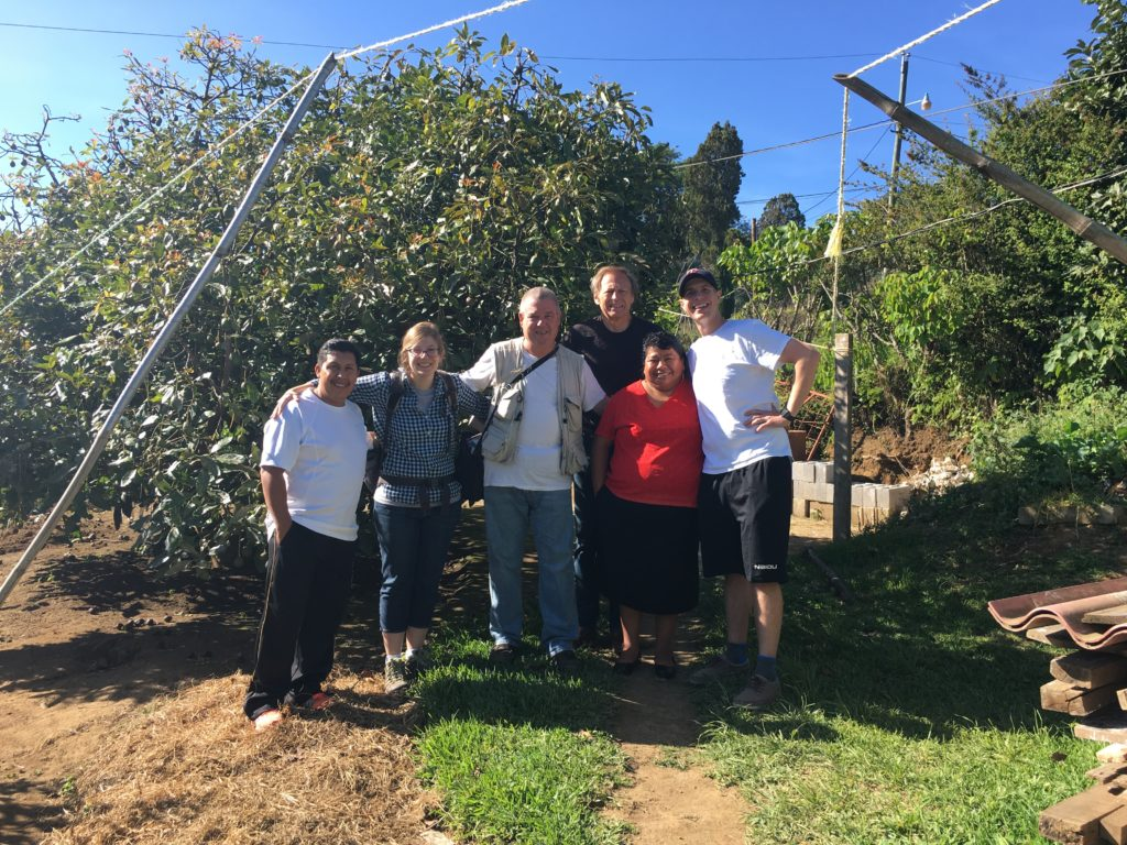 Two Guatemalans and four Americans stand in an orchard at the height of summer