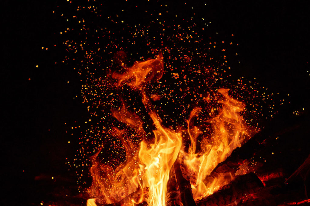 Embers fly upward from a bright fire against a black sky