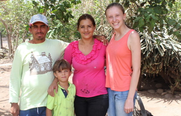 A Nicaraguan family and a young American woman, all wearing colorful clothing, stand under a tree on a sunny day