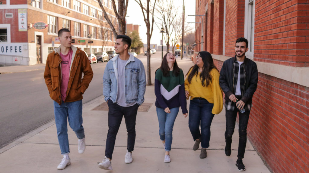 University students walking five abreast on a sidewalk on a fall day