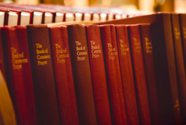 Copies of a red-covered book sit in a row on a wooden shelf. The cover reads, The Book of Common Prayer.