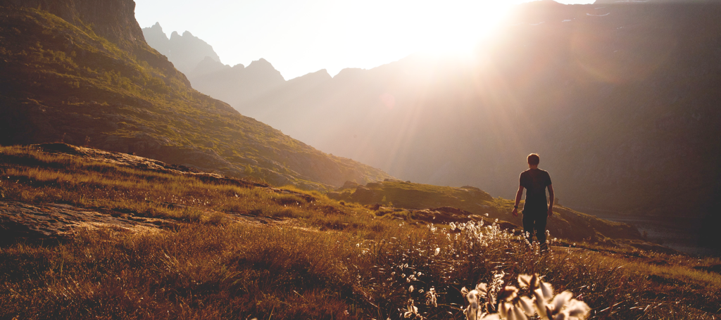 Sun rays shining over mountain ridge with man looking in the distance