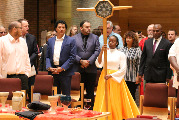A confident young woman in flowing dancer's attire carries a cross into a worship space as worshipers look on.