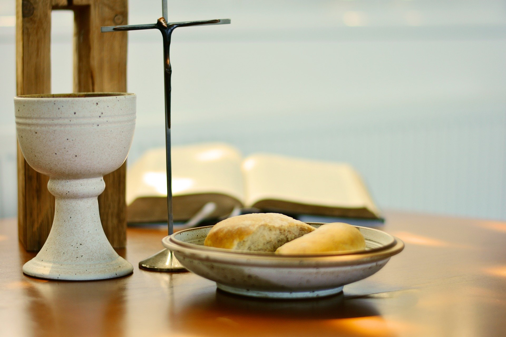 The table is set for Communion with a stone cup and a broken bread loaf on a matching stone dish. A slender metallic cross and open Bible are in the background.