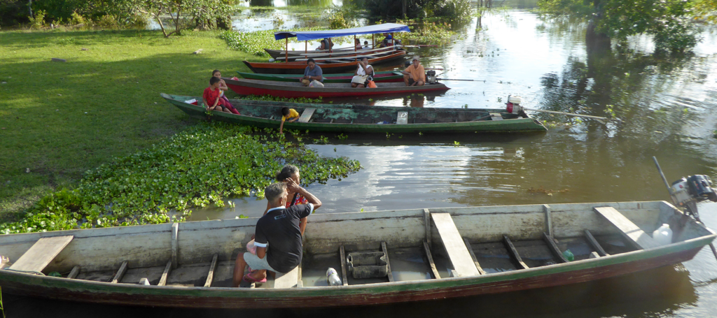 six canoes on a river bank with several people in each one