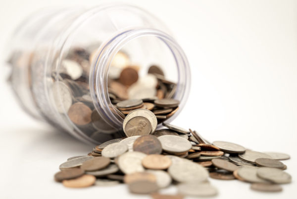 A jar of coins laying on its side, with the coins spilling out