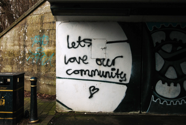 Graffiti painted on wall under a bridge that says let's love our community