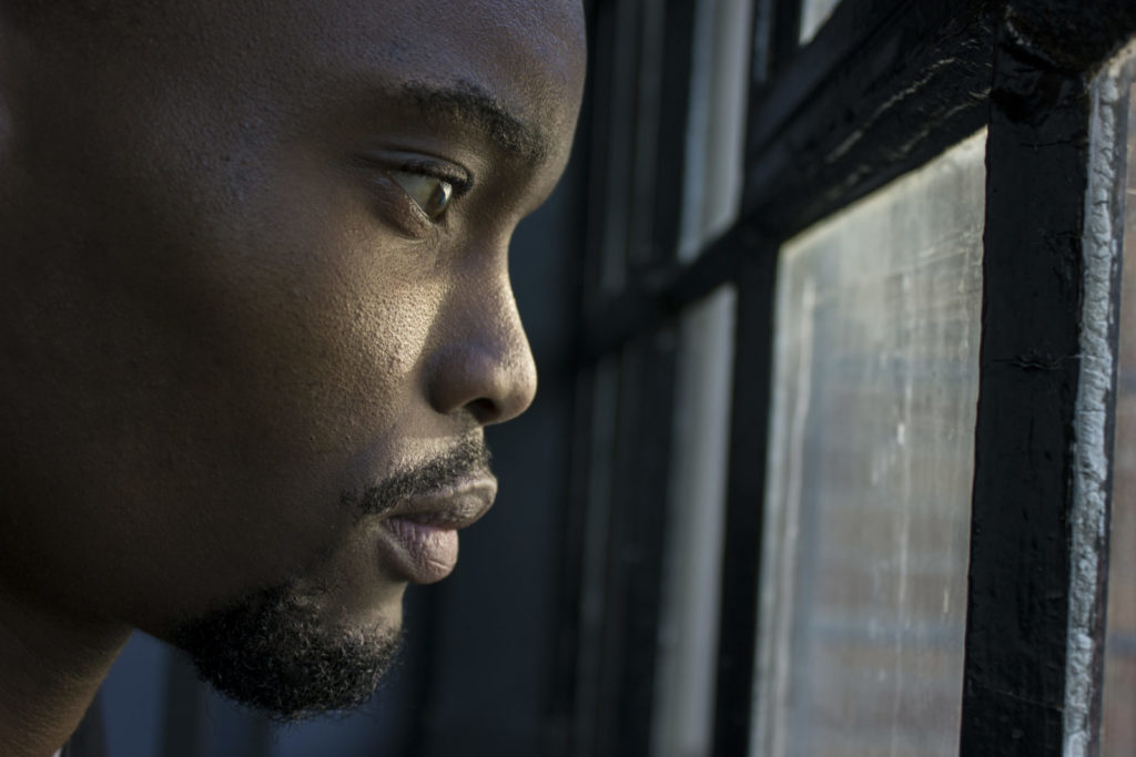 Side profile photo of a man looking anxiously out a window, as many people around the world find themselves doing because of the Coronavirus outbreak.