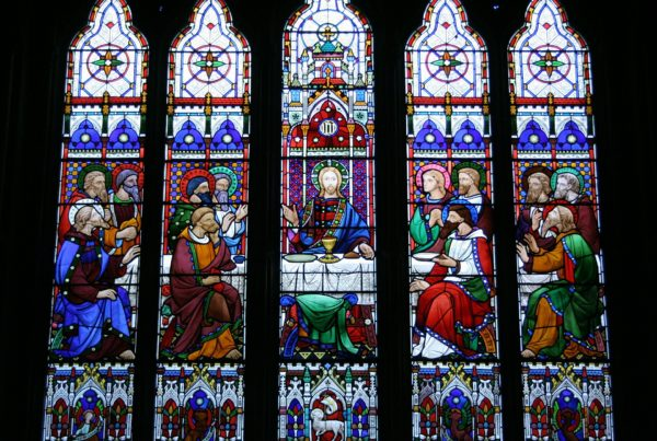A series of five narrow stained-glass windows portrays Jesus and the disciples at the Last Supper.