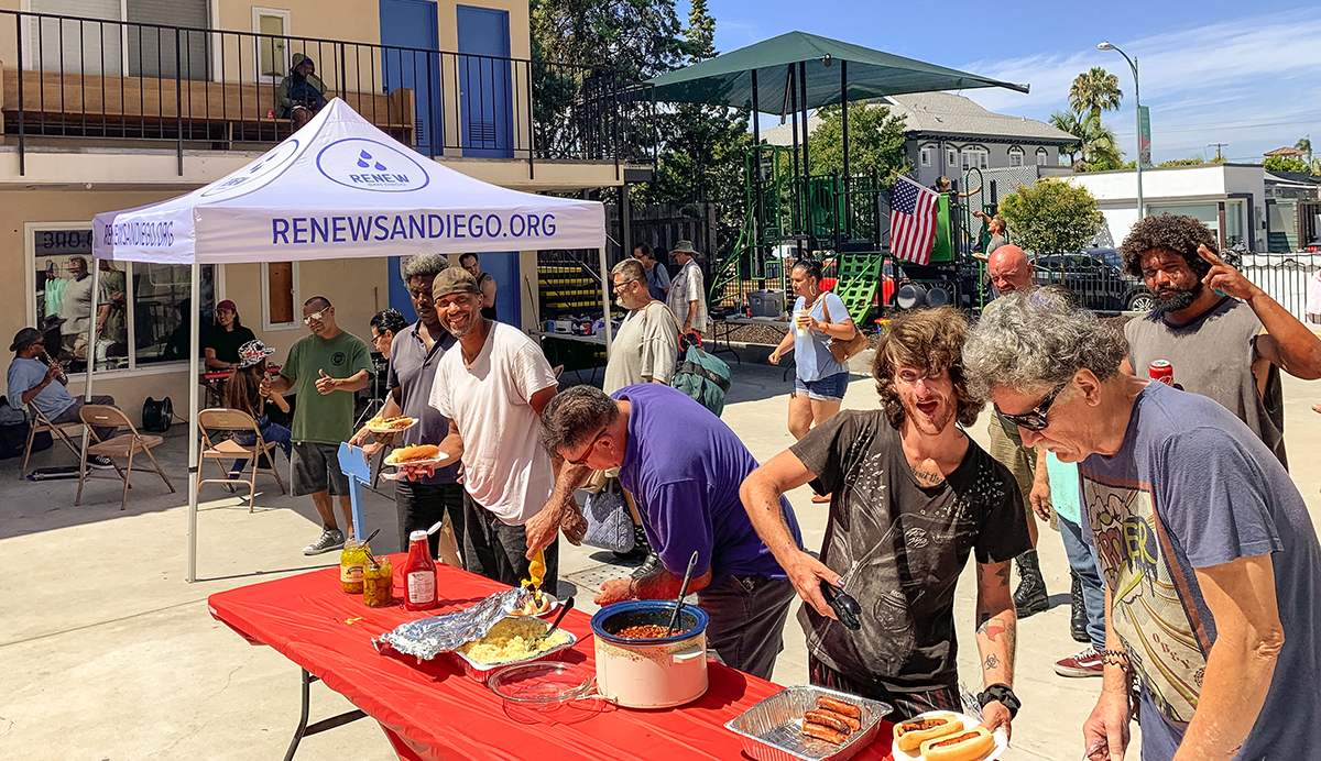 Community members flash smiles and grins as they fill up their plates from a church buffet line.