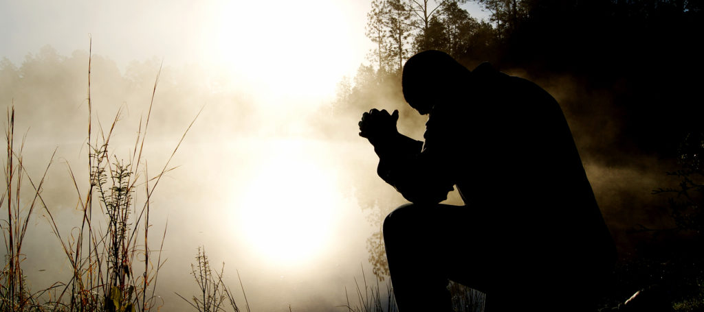 Silhouette of a man with elbows on his knees and hands folded in prayer