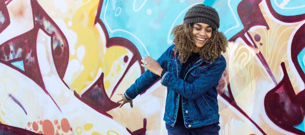 AFrican-American young lady standing by painted wall