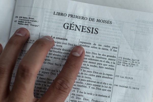 Hand on Bible that is open to Genesis 1