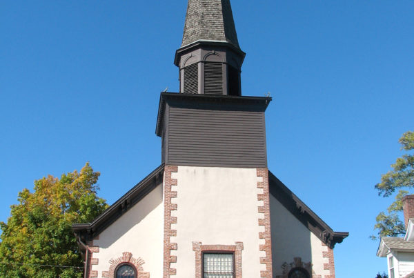 A tan church with wooden doors and a gray steeple stands tall against the clear blue sky.