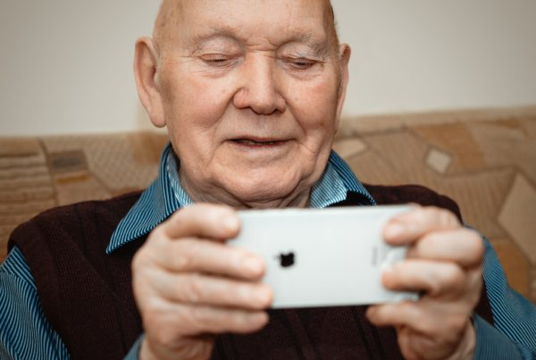 Older man using an iPhone to FaceTime, as many of us are dong now to stay connected during the coronavirus pandemic