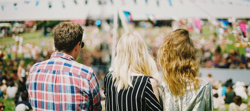 View from behind a man and 2 women looking out at a crowd that is blurred in the background