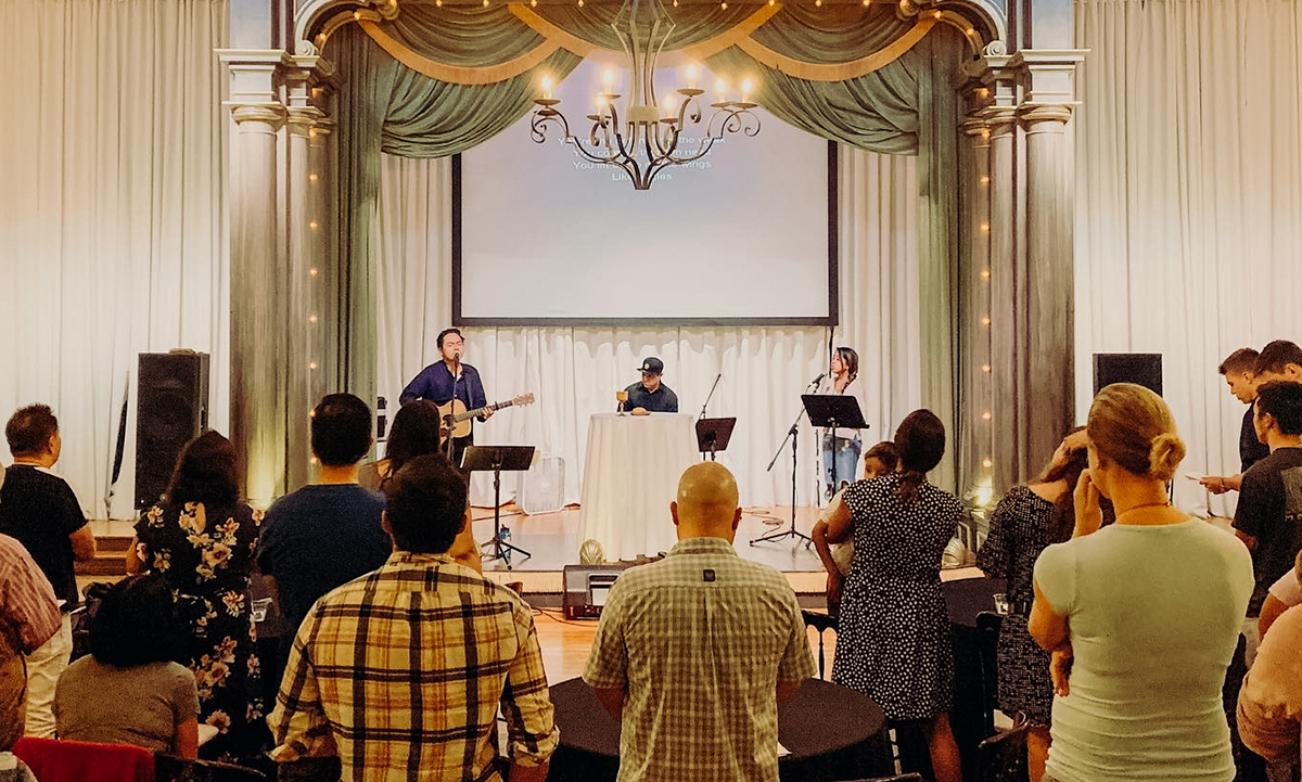 People stand around round tables, facing forward and led in worship by a guitarist and a singer on stage.