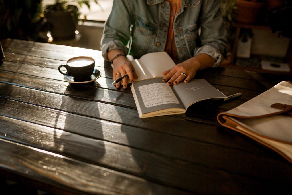 person journaling in a notebook on brown wooden table