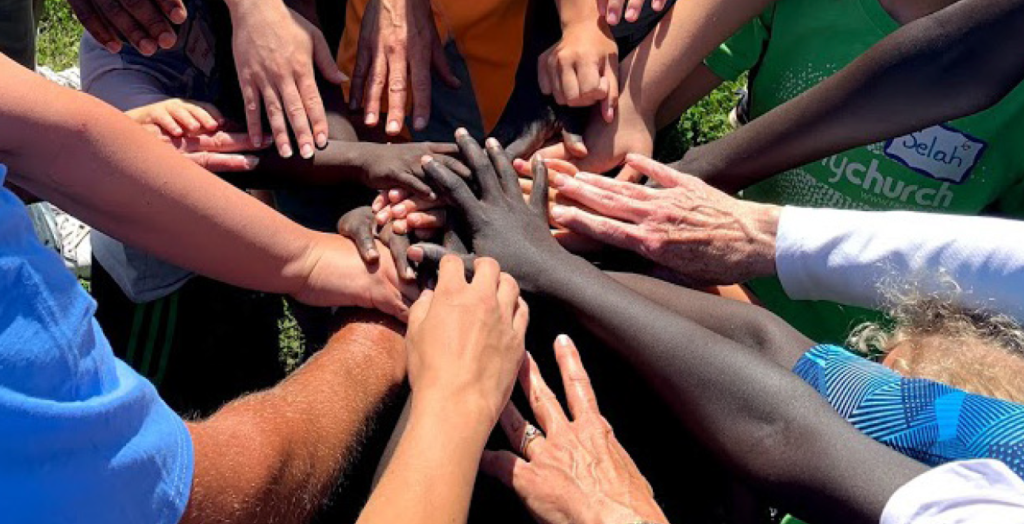 multi-ethnic arms outstretched with hands meeting in the middle